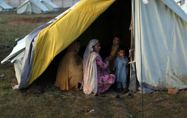 An internally displaced family, fleeing military operations in Buner, sits in a tent at a UNHCR camp in Mardan