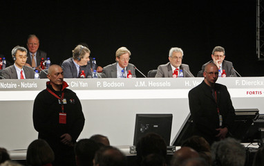 The board of directors of Dutch-Belgian financial services sit behind security guards during a shareholders meeting in Brussels