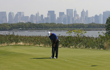 New York's lower Manhattan skyline is seen in the background as Tiger Woods of the U.S. putts on the 14th hole