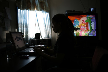 Elvira Arellano sits at her computer as her son watches cartoons in their apartment inside Adalberto United Methodist Church in Chicag