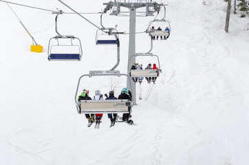 People ride the ski chair lift up the mountain together while sitting closely to each other having a fun time during a day of snowboarding