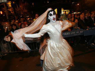 A scary bride runs through the streets at the Village Halloween Parade in New York