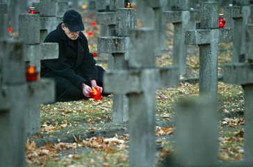 Polish man lights a candle at Powazki military cemetery on All Saints Day in Warsaw
