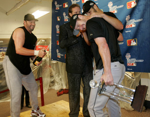 Houston Astros' Roger Clemens sprays champagne on Astros' Roy Qswalt in the locker room after defeating the St Louis Cardinals St Louis
