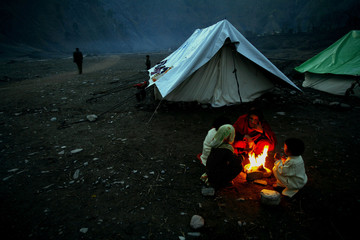 Kashmiri women and children try to keep warm over an open fire at Mustafai relief camp located in Th..