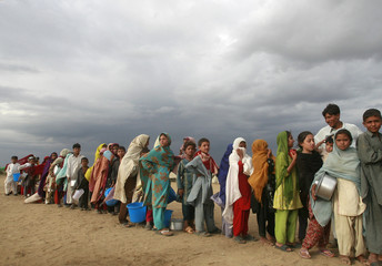 Internally displaced children stand in-line for their ration of food at the UNHCR camp in Swabi district