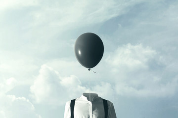 surreal man with big black balloon suspended over his head