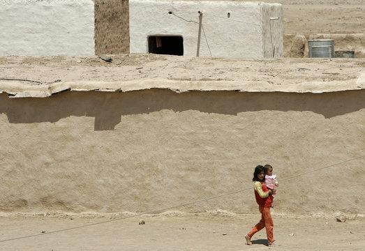 A girl carries a baby as she walks in Kahtaniya