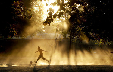 A Chilean plays soccer at a park on last day of summer.