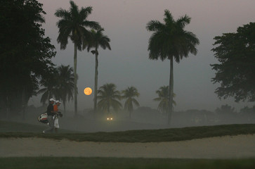 Golfer Weir of Canada and his caddy walk up the first fairway under a full moon during his practice round for the CA Championship at Doral Golf Resort in Miami