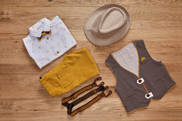 Top view photo of the boy's clothes with accessories on the wooden background.