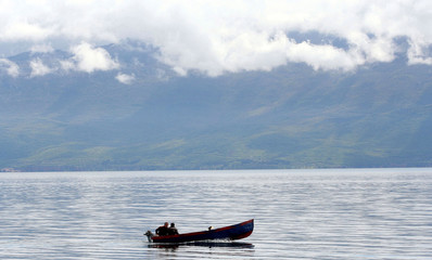 Albanian fishermen row their boat in the Ohrid lake in the city of Pogradec