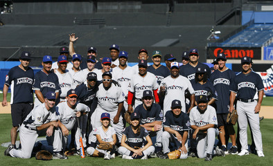 Participants in the Legends and Celebrities All Star softball game pose for a photograph following the game at Yankee Stadium in New York