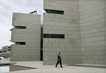 An employee walks across the low-lying metal and glass constructions that make up Santander Central ..
