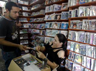 A customer buys pirated CDs and DVDs at a marketplace in Asuncion, a day before the country holds presidential elections