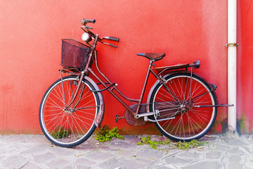 Old bicycle on a red wall background