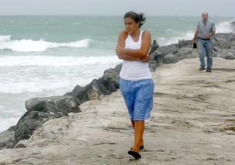 Beach goer Connie Arias of Miami Beach walks along a jetty on Miami Beach