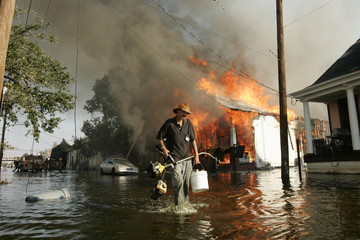 A man makes his way out of flood waters as a home burns in the seventh ward of New Orleans during the aftermath of Hurricane Katrina