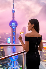 Elegant asian woman in gown drinking white wine glass at rooftop bar terrace looking at city lights skyline view of Shanghai in sunset. Luxury travel or high end lifestyle.