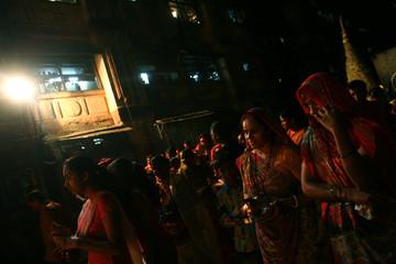 Indian hindu women watch a ritualistic bonfire that marks the beginning of 'Holi' the Hindu festival of colour in Mumbai