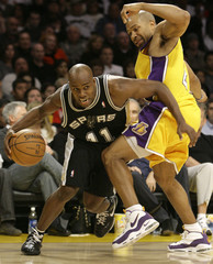 San Antonio Spurs' Jacque Vaughn draws a foul as he drives around Los Angeles Lakers' Derek Fisher during the first half of their NBA basketball game in Los Angeles