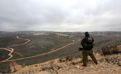 Israeli soldier stands near unauthorized outpost of Amona close to West Bank Jewish settlement of Ofra