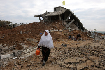 Palestinian woman carries gas container salvaged from ruins in Jabalya