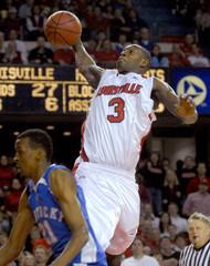 University of Louisville's Juan Palacios shoot over top University of Kentucky's Perry Stevenson in Louisville