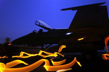 BOMB LADEN HORNET IS LIT BY A FULL MOON ON BOARD USS ABRAHAM LINCOLN INTHE GULF.