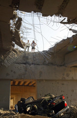Lebanese civilians look at destroyed car that crashed through bridge which was attacked by Israeli warplanes in Jadra