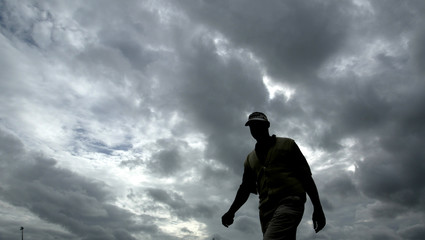 FIJI'S VIJAY SINGH WALKS UNDER A STORMY SKY ON THE FIRST DAY OF THEBRITISH OPEN AT ROYAL ST GEORGE'S IN ...