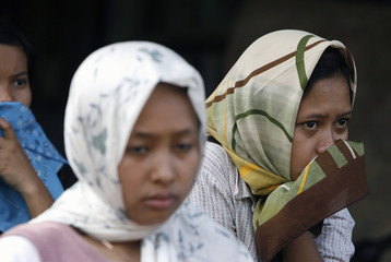 Women watch as an excavator destroys their house during eviction in Jakarta