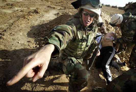 A wounded Iraqi man is treated by U.S. marines as he begs to be released to see his injured family m..