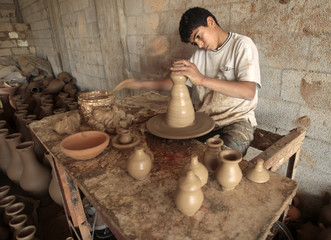 A Palestinian boy makes clay pots in a pot factory in the central Gaza Strip