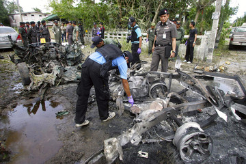 Police officers survey the site of a bomb attack in Narathiwat province