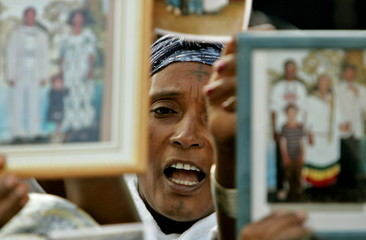 An Ethiopian immigrant holds up pictures of relatives still living in Ethiopia during a demonstratio..