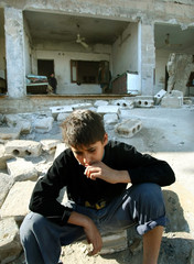 PALESTINIAN BOY SITS IN FRONT OF DEBRIS OF HIS HOUSE AFTER ISRAELIMILITARY THRUST IN GAZA CITY.