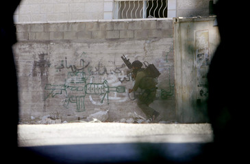 An Israeli soldier takes position during a military operation in Jenin