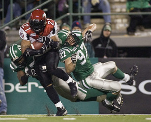 Calgary Stampeders Reynolds takes a hit from Saskatchewan Roughriders Chick during the second half of their CFL play-off football action in Regina