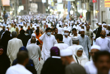Muslims wearing medical masks walk outside the Grand Mosque after night prayers during the holy month of Ramadan in Mecca