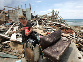 Cuban woman holds onto to thermo she found underneath rubble of destroyed house.