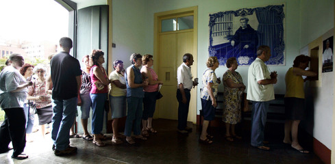 """Pilgrims line up to receive """"miracle pills"""" created by Frei Galvao at the Luz Monastery in Sao Paulo"""