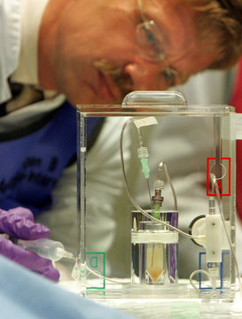 Nuclear physician Tatsch looks at a radiation liquid during an operation on a cancer patient by the new radiation treatment for liver tumours SIRT in Munich's university hospital