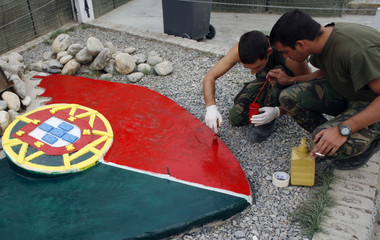 Soldiers from Portugal's ISAF contingent paint a symbol of their unit inside their base at Camp Warehouse in Kabul