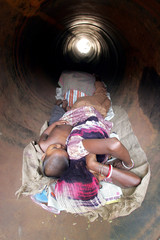 A homeless Indian woman and her child sleep inside a drain pipe on a hot summer day in Calcutta.