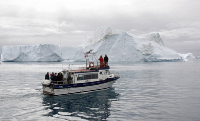A boat sails through Ilulissat fjord in Greenland