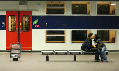A couple kisses while waiting for train at Gare du Nord train station in Paris
