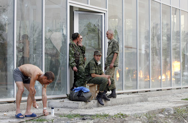 A Russian soldier washes near a house which was set on fire by South Ossetian militia in the Georgian village of Kvemo-Achebeti