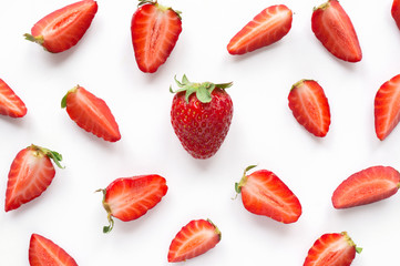 Fresh red strawberry with sliced berries pattern. Food background. Top view.
