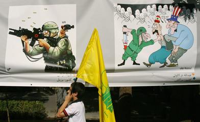 Boy carrying the flag of Lebanese Hezbollah walks past anti-Israeli cartoons during Jerusalem Day demonstration in Tehran